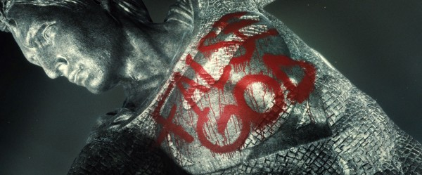 """Superman também é alvo de desconfiança e revolta.  Uma estátua erguida em sua homenagem está pichada com os dizeres """"Falso Deus"""""""