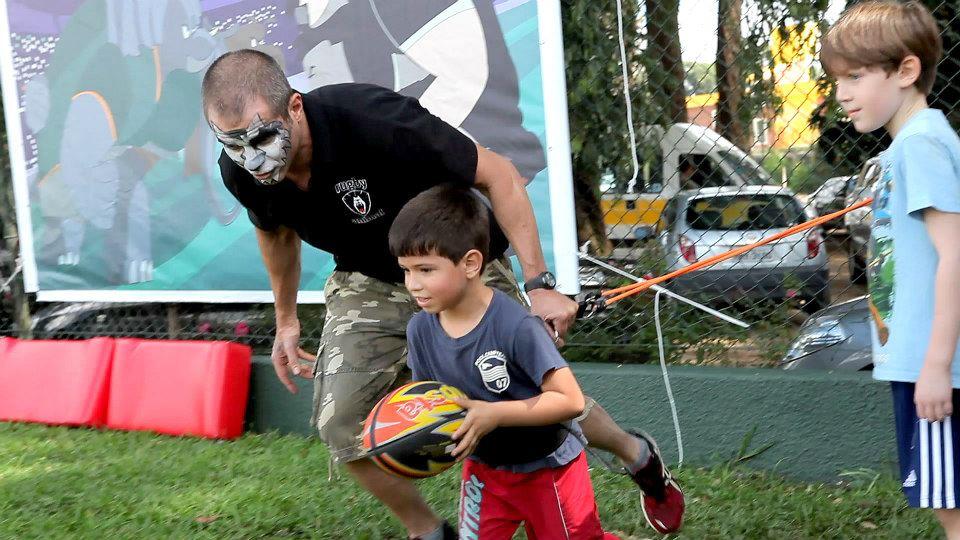 """Professo do projeto """"Rugby Animal"""" orienta criança durante evento"""