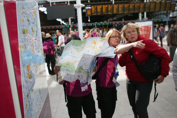 Voluntárias auxiliam turista no metrô de Londres, durante os Jogos de 2012