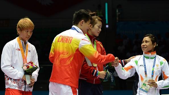 A indiana Sarita Devi recebe a solidariadade das demais lutadoras, enquanto a coreana Jina Park apenas observa a cena