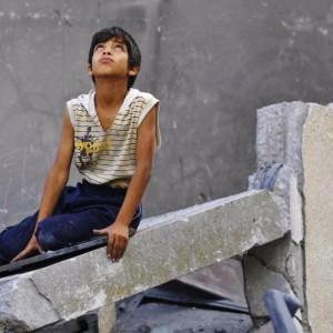 Menino palestino nos destroços de um prédio destruído em Gaza - MOHAMMED ABED / AFP