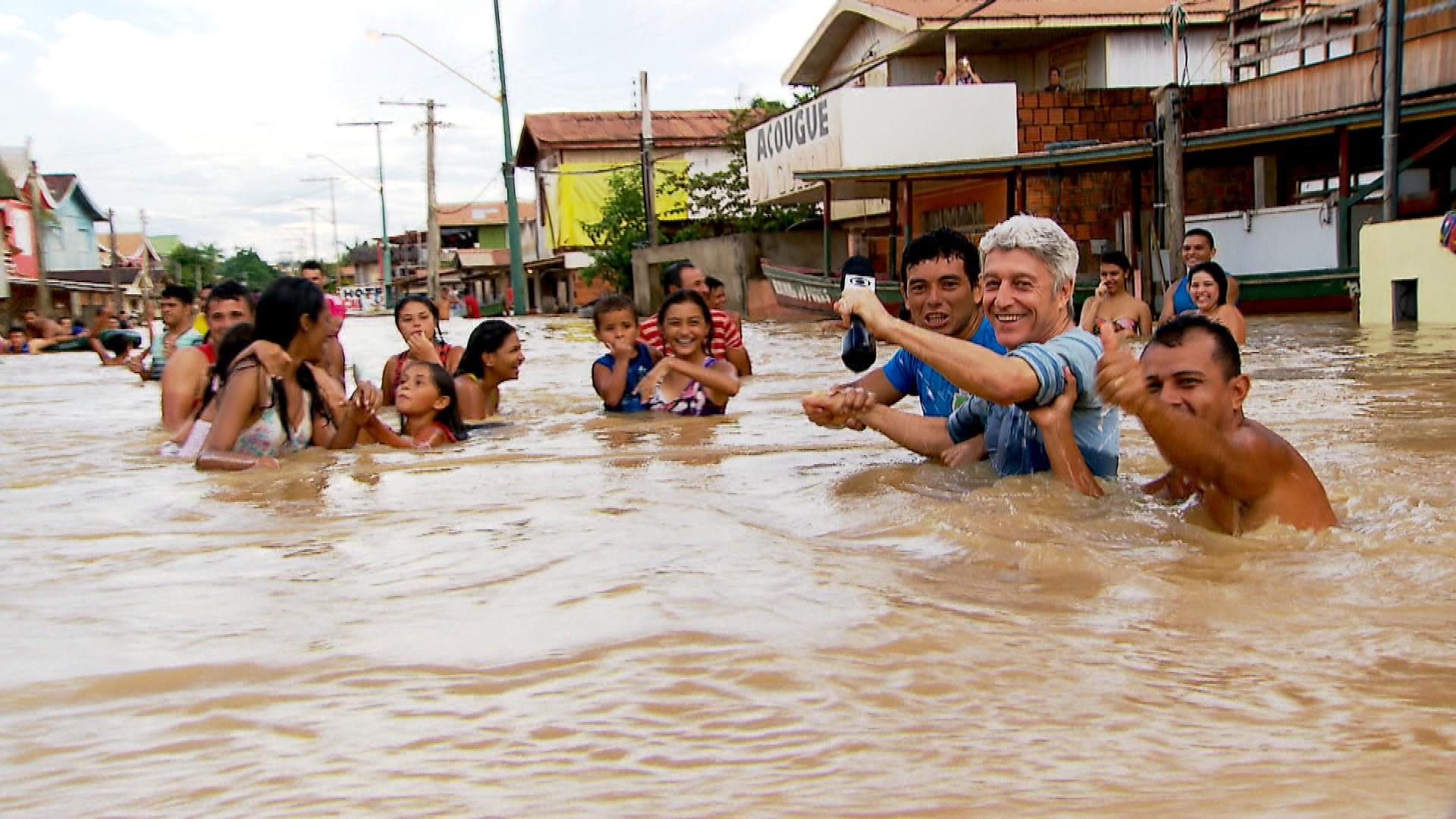 Moradores de Boca do Acre ajudam Caco Barcellos a enfrentar a correnteza das ruas alagadas (Fotos: Divulgação/Globo)