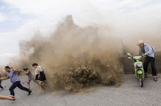 Visitors run away as waves from a tidal bore surge past a barrier on the banks of Qiantang River, under the influence of Typhoon Trami, in Hangzhou, Zhejiang province -0XFK0786.jpg-