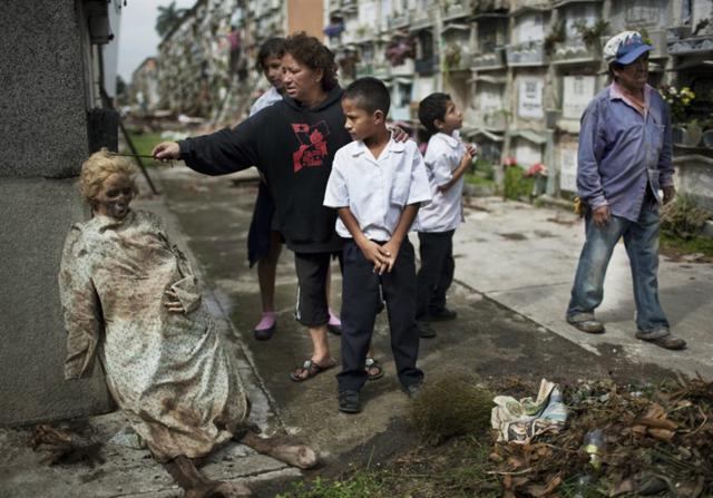 Corpo exumado de seu túmulo e deixado apoiado na parede, num cemitério da Guatemala, após parentes não conseguirem pagar as taxas do cemitério.