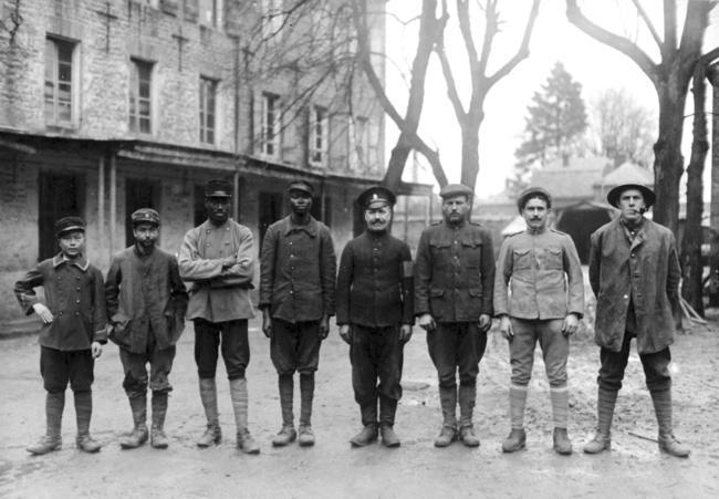 Soldados aliados, representando oito nacionalidades diferentes. A partir da esquerda: vietnamita, tunetano, senegalês, sudanês, russo, americano, português e inglês, no desconhecido campo de prisioneiros alemão em 1918