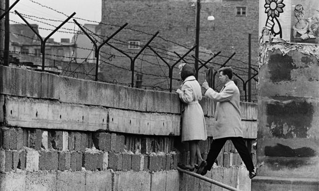 Um jovem casal de Berlim Ocidental agarrado no muro enquanto a mulher fala com a mãe, 1960.