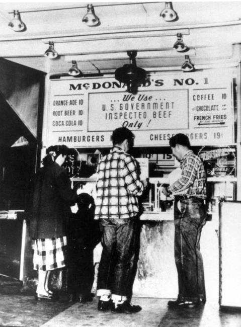 Clientes se alinham dentro da primeira lanchonete McDonalds, inaugurada em 1948, na Califórnia.