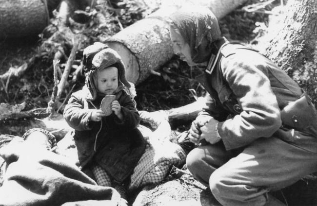 Soldado alemão dando pão a um menino órfão russo, em 1942.