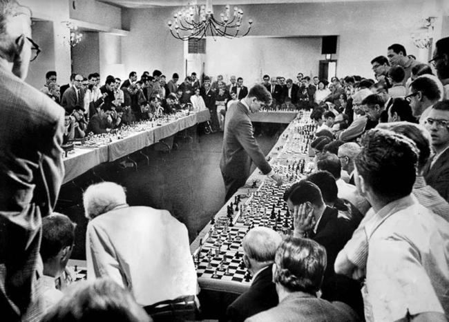 O prodígio Bobby Fisher jogando com 50 oponentes simultaneamente em um hotel em Hollywood, em 12 de abril de 1964. Ele venceu 47, perdeu um e empatou dois.