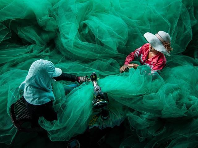 Mulheres costurando uma rede de pesca no Vietnã