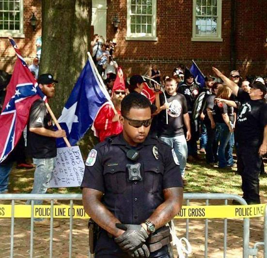 Policial negro protegendo o direito de protesto de um grupo pró-nazismo