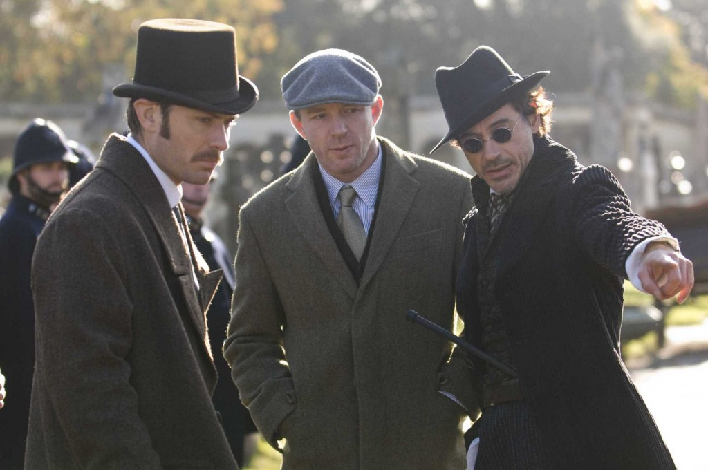 Guy Ritchie entre Jude Law e Robert Downey Jr.: maneirismos do cinema independente a serviço de blockbusters (Foto: Divulgação)