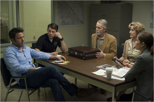 Nick Dunne e os pais de sua esposa em uma conversa com a polícia: filme que se revela em camadas