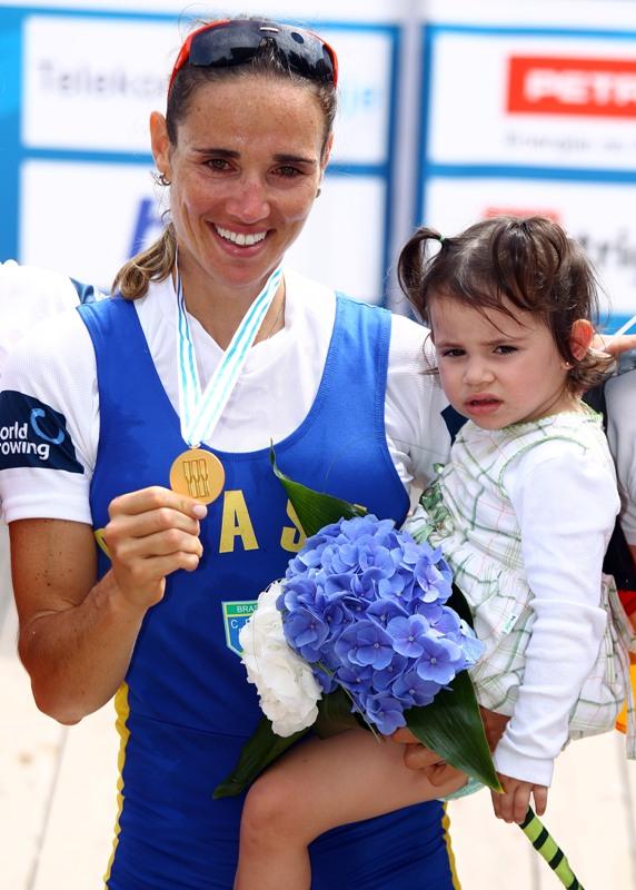 A remadora brasileira Fabiana Beltrame comemora no pódio, ao lado da filha, a medalha de ouro no Mundial de 2011, na Eslovênia