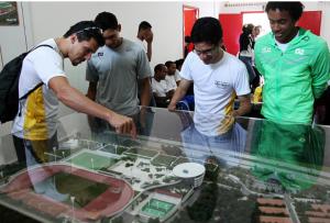 Atletas observam a maquete do futuro centro de treinamento