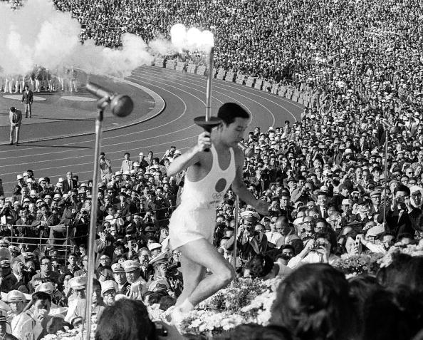 O jovem Yoshinori Sakai, que nasceu no dia em que a bomba nuclear destruiu Hiroshima, sobe a arquibancada para acender a pira olímpica em 1964